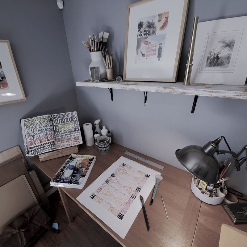 Photo of part of Bruce Black's art studio.  A lamp and various paintings are shown along with a watercolor palette.
